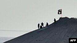 """Кобани маңында """"Ислам мемлекеті"""" экстремистік ұйымы туын көтерген содырлар деп жарияланған сурет. Сирия, 7 қазан 2014 жыл. (Көрнекі сурет)"""