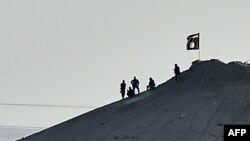 Вооруженные мужчины, предположительно боевики ИГ, на горе, на вершине которой водружен флаг ИГ, близ сирийского города Кобани. 7 октября 2014 года.