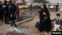 Жінка з дитиною йдуть повз місце вибуху в Багдаді, 9 лютого 2015 року