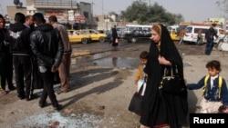 Ирак астанасында жарылыс болған жердің қасынан балаларын жетектеп өтіп бара жатқан әйел. Бағдад, 9 ақпан 2015 жыл. (Көрнекі сурет)