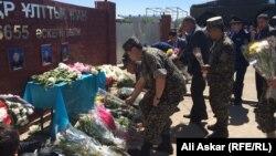 Люди несут цветы к портретам военнослужащих, убитых при атаке на воинскую часть 6655 в Актобе. 9 июня 2016 года.