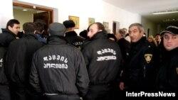 Грузинская полиция безопасности голосовала, прикрывая друг друга широкими спинами