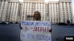 Жена протестира против донесувањето на законот пред парламентот во Москва.