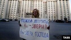 Жінка проводить одиночний пікет біля Державної думи Росії, протестуючи проти закону про заборону всиновлення російських дітей громадянами США, 19 грудня 2012 року
