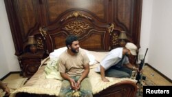 Rebel fighters sit on a bed at embattled Libyan leader Muammar Gaddafi's farm house near the town of Abu Grein on the way to Sirte, August 30.