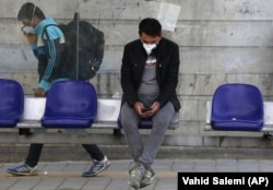 A man wearing a face mask to protect against the coronavirus sits at a bus stop in Tehran.