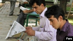 Iran, Tehran -- two young man read newspaper