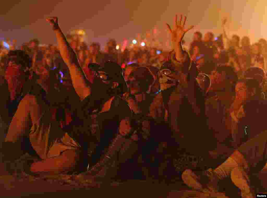 "Jed Vassallo (left) and Erin Bohlmann cheer as the ""man"" burns during the Burning Man 2013 arts and music festival."