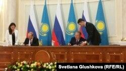 Президент Казахстана Нурсултан Назарбаев (сидит справа) и президент России Владимир Путин подписывают документы по итогам встречи. Астана, 15 октября 2015 года.