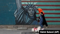 A woman walks her dog past a wall of the former U.S. Embassy in Tehran.