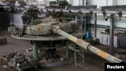 An employee works on a tank turret as armored vehicles are repaired at a Kyiv armored plant on August 14.