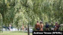 Codul portocaliu de caniculă și temperaturile de aproximativ 40 de grade Celsius din vara aceasta i-a dus pe mulți oameni să se relaxeze la soare, în parcuri. În această fotografie, oamenii fac plajă lângă Parcul Alexandru Ioan Cuza din București.
