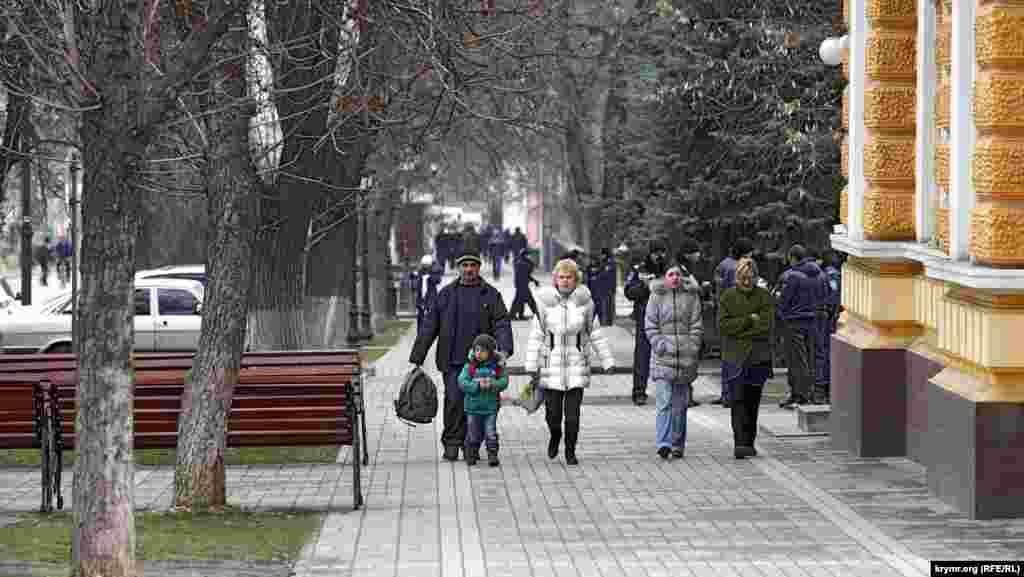За лентой жизнь идет своей чередой. Это улица Горького, там, где на нее выходит тыльная сторона здания Верховной Рады Крыма. Обывателей то, что происходит с обратной стороны квартала, совершенно не интересует.
