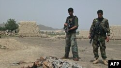 Afghan soldiers stand near the body of a suicide attacker near U.S. Camp Salerno on the outskirts of Khost city.