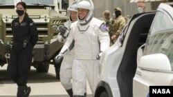 Астронавтите на НАСА Дъглас Хърли (ляво) и Робърт Бенкен, облечени в космическите костюми на SpaceX, вървят към Falcon 9 на 27 май 2020 г.