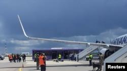 A reptéri személyzet és a biztonsági erők láthatók az aszfalton egy Ryanair-járat előtt, amely kénytelen leszállni Minszkben, 2021. május 23-án