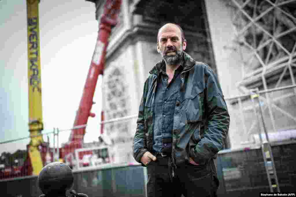Vladimir Iavachev, nepotul lui Christo, pozează în fața Arcului de Triumf din Paris. După ce înfășurarea arcului a fost amânată din cauza pandemiei de coronavirus, iar Christo a murit în mai 2020, munca de supraveghere a proiectului i-a revenit lui Vladimir.