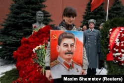 A woman holds a picture of a Soviet leader Josef Stalin during a ceremony marking the 66th anniversary of his death in Moscow's Red Square on March 5.