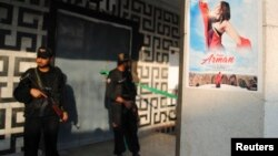 Pakistani policemen guard the entrance of a cinema at the site of a deadly attack in Peshawar on February 11.