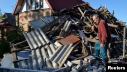 A man removes debris in front of his house, which was damaged by recent shelling in the government-held town of Avdiyivka last month.