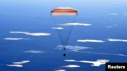 The Russian Soyuz MS-02 space capsule carrying the International Space Station (ISS) crew descends toward a remote area in Kazakhstan.