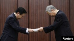 Yotaro Hatamura (right), a University of Tokyo engineering professor and the head of a government-appointed panel investigating the cause of the Fukushima nuclear crisis, hands over the final report to Japan's Prime Minister Yoshihiko Noda in Tokyo.