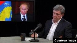 Григорий Явлинский в эфире программы «Лицом к событию» на фоне изображения Владимира Путина.