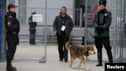A Cossack (right) and a police officer (left) stand guard outside Sochi's main train station as a dog passes on January 17, with security measures already tight ahead of the Winter Olympics scheduled to begin on February 7.