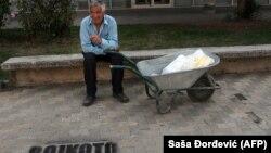 """Stanovnik Bujanovca pored natpisa na albanskom """"Bojkot referenduma"""" 2011. godine, arhivska fotografija. Albanska zajednica je bojkotovala popis jer su listići bili štampani samo na srpskom jeziku"""