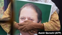 A supporter of ousted former Pakistani prime minister Nawaz Sharif held his picture at the venue where his younger brother Shahbaz Srarif led a rally towards the airport in ahead of the arrival in Lahore on July 13.