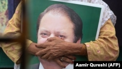 FILE: A supporter of former Pakistani Prime Minister Nawaz Sharif holds his picture at Lahore airport ahead of his arrival in July 2018.