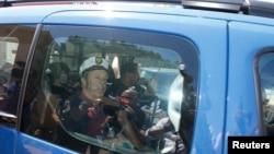 Расейскіх заўзятараў вязуць у паліцэйскай машыне 14 чэрвеня.