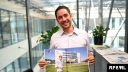 Zachary Peterson poses with the center spread on RFE/RL's headquarters in the recent issue of Era 21 magazine.