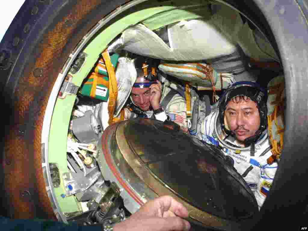 """Космонавт Талгат Мусабаев (справа) и космический турист Деннис Тито после приземления посадочной капсулы """"Союз"""". Окрестности города Аркалык, 6 мая 2001 года."""