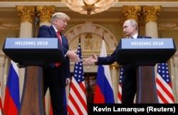 U.S. President Donald Trump (left) and Russia's President Vladimir Putin shake hands during a joint news conference after their controversial summit in Helsinki on July 16.