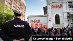 Полицейский на фоне театра «Гоголь-центр» и его посетителей в Москве.