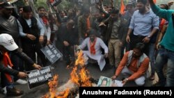 Activists from a right-wing Hindu group burn portraits of Pakistani Prime Minister Imran Khan as tensions rise between India and Pakistan.