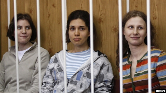 "Members of female punk band ""Pussy Riot,"" Nadezhda Tolokonnikova (center), Maria Alyokhina (right), and Yekaterina Samutsevich, sit behind bars before a court hearing in Moscow on July 20."