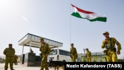 FILE: Tajik Servicemen of the Panj Border Service detachment walk at the Somon border outpost on the Tajik-Afghan border on August 14.