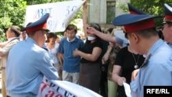 Полицейлер сөз бостандығын қорғау шарасын ұйымдастырушылардың ұрандарын тартып алып жатыр. Алматы, 24 маусым 2009 жыл