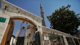Мужчины ремонтируют дверь у входа во двор мечети в Башчаршии, историко-культурном центре Сараеве.