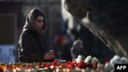 Женщина ставит свечу жертвам советских политических репрессий у Соловецкого камня на Лубянке в Москве