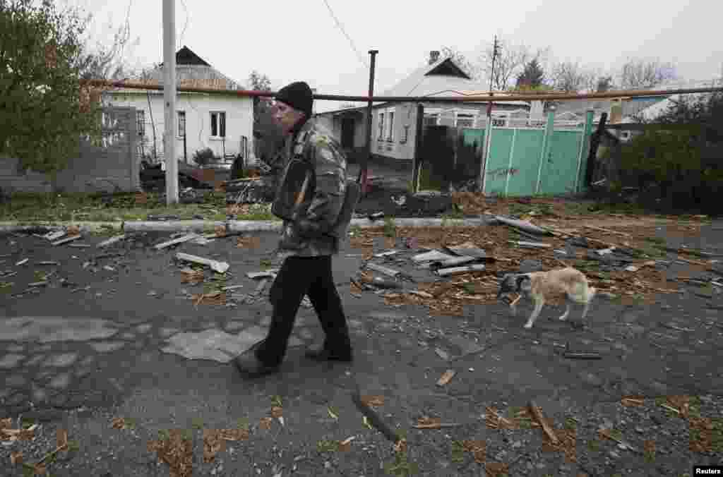 Vladimir Shramko, 48, walks past his neighbor's house, which was damaged by shelling, in the village of Spartak on the outskirts of Donetsk in October 2014.