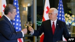 Georgian Prime Minister Giorgi Kvirikashvili (left) raises a toast with U.S. Vice President Mike Pence during an official dinner in Tbilisi on July 31.