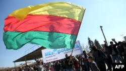A Kurdish man waves a large flag of the Kurdish People's Protection Units' (YPG) political wing, the Democratic Union Party (PYD), during a demonstration against the exclusion of Syrian Kurds from the Geneva talks on Syria in February.