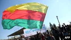 A man waves a flag of the Kurdish People's Protection Units, the military wing of the Democratic Union Party, at a demonstration in the Syrian city of Qamishli on February 4, 2016.