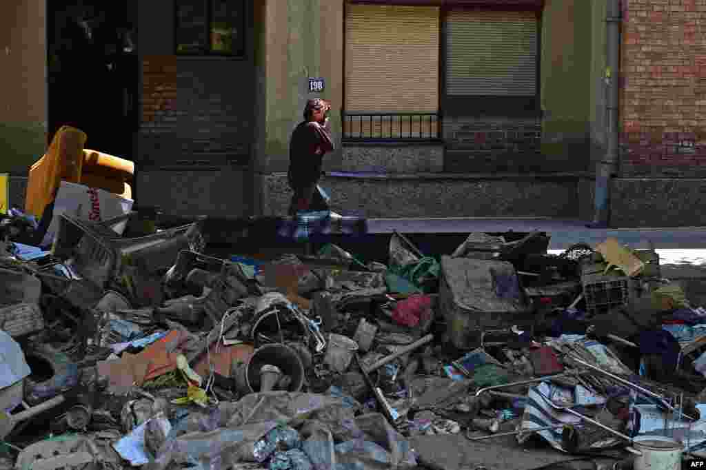 A woman walks past piles of rubbish in the Serbian town of Obrenovac in the wake of some of the country's worst ever floods. (AFP/Andrej Isakovic)