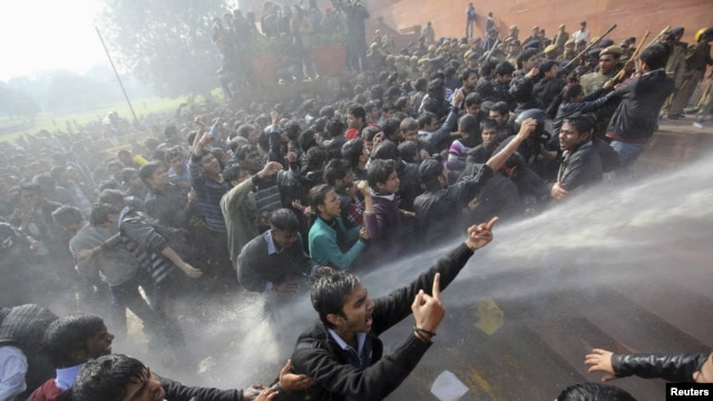 Demonstrators shout slogans as police use water cannons to disperse them near the presidential palace during a protest rally in New Delhi on December 22, following the gang rape of a woman on a municipal bus.