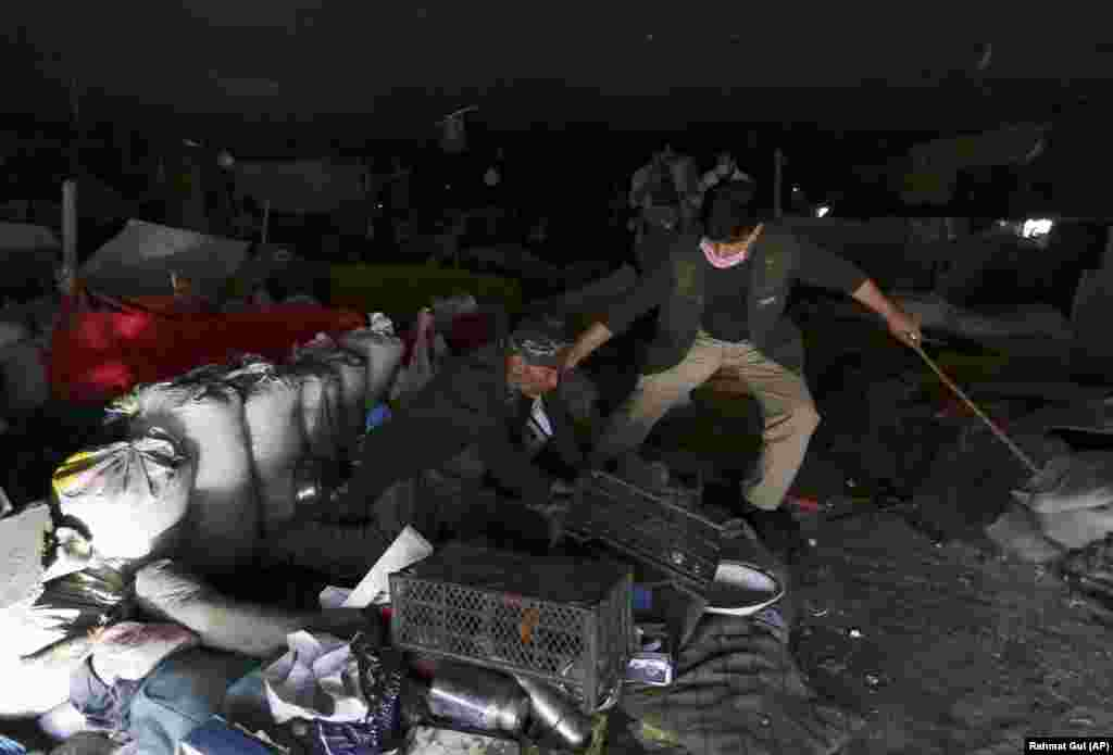 АВГАНИСТАН - Припадник на авганистанските безбедносни сили приведува лице осомничено за употреба на дрога. Властите во Кабул спроведоа голема акција против илегалната употреба на опојни дроги.