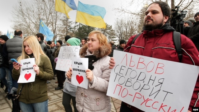 "Demonstrators hold banners reading ""Lviv speaks Russian language today!"" at a rally near the parliament building in Simferopol, Crimea, on February 26."